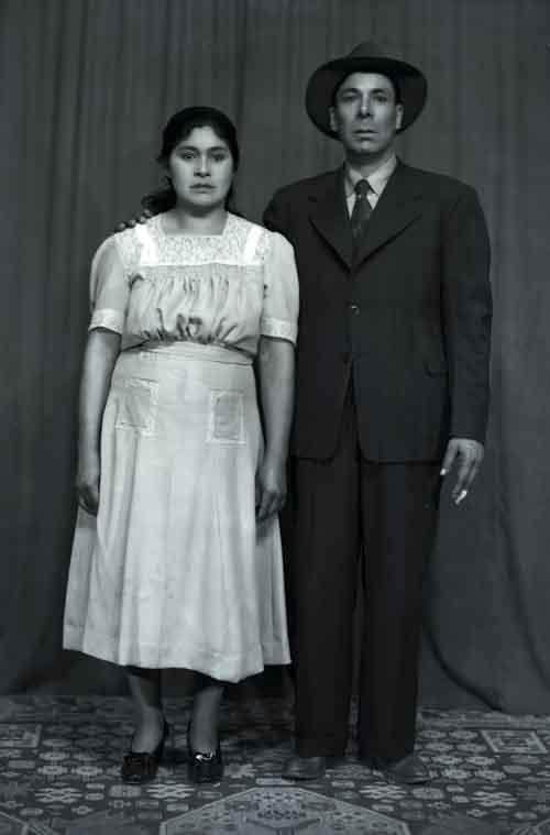 Retrato de mujer joven con vestido formal y hombre adulto con traje y sombrero en estudio (atribuido)
