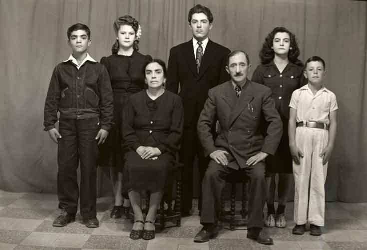 Retrato de familia de siete integrantes, madre y padre con dos mujeres y tres hombres con ropa formal en estudio (atribuido)