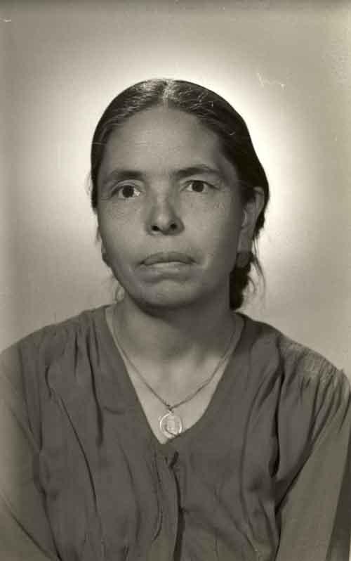 Retrato de mujer adulta con vestido formal y medalla religiosa en pecho en estudio (atribuido)