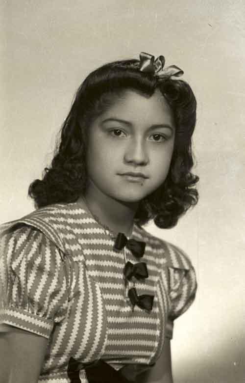 Retrato de niña con vestido formal y peinado con moño en estudio (atribuido)